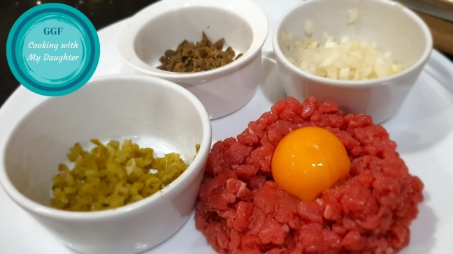 Tartare de boeuf au couteau. Image showing finely hand-chopped fillet steak with an egg yolk in the centre and small bowls containing the seasonings on the side - one with finely chopped gherkins, one with finely chopped capers and the third with finely chopped onions.
