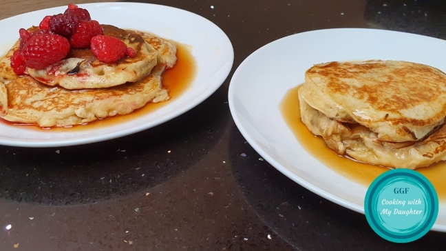 Pncakes with Logo. Image shows two plates on a black worktop which each have 2 pancakes on covered in maple syrup. The left hand plate of pancakes has a few raspberries on top.